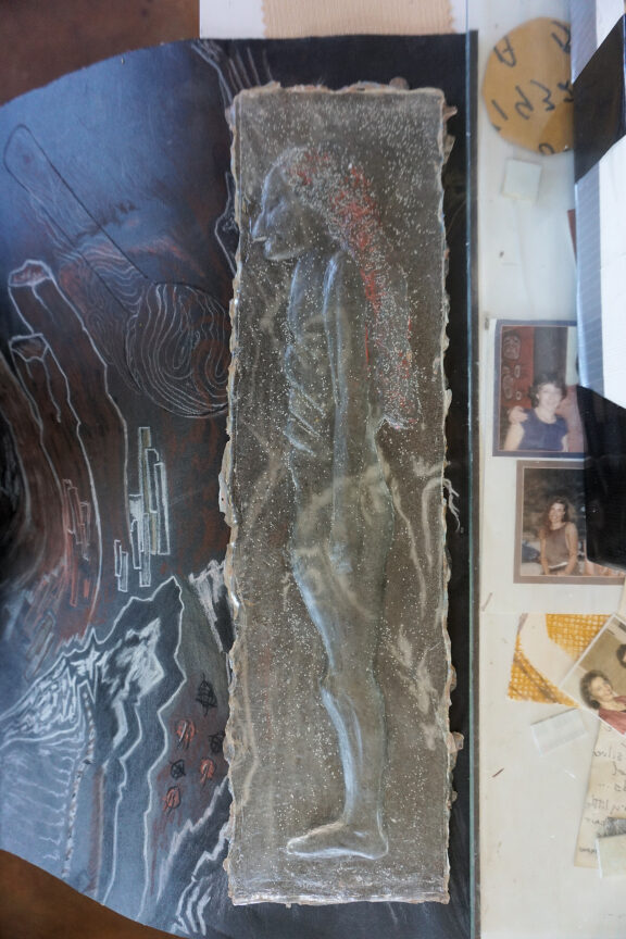photo of clear resin cast bas relief figure on conte drawing
