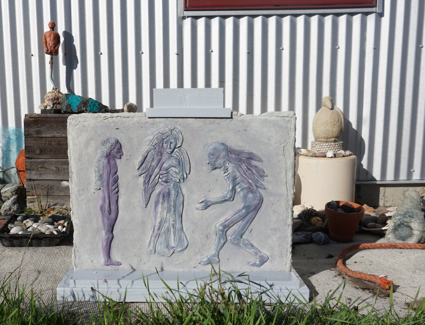 Photo of relief cement cast of Three Angels: The Mediation in wooden stand outside my Studio
